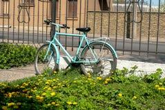 单独站立在篱芭附近的自行车 库存图片