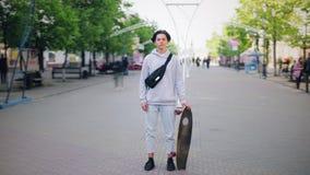 单独站立在街道藏品滑板的年轻男孩定期流逝 股票视频