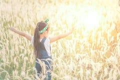 单独站立在领域的孩子在美好的日落期间 免版税库存图片