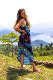 单独站立狂放的森林湖的年轻欧洲美女在背景 图库摄影
