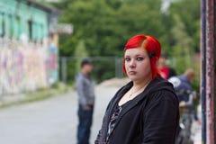 单独红色听见的妇女在城市 库存图片