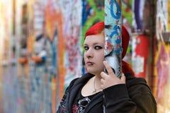 单独红色听见的妇女在城市 库存照片