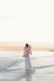 单独美丽的女孩有桃红色鸟的海的在日落 库存照片