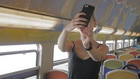 单独美丽的白种人女性游人采取在一列空的地铁的一selfie 享受孑然的概念 ? 影视素材