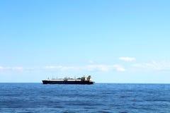 单独航行在蓝色海洋中间的船 库存照片