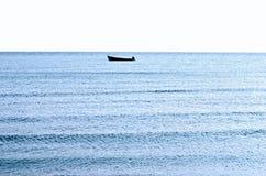 单独航行在镇静蓝色海。 库存照片