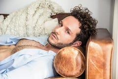 单独说谎在长沙发的赤裸上身的性感的男性模型 库存图片