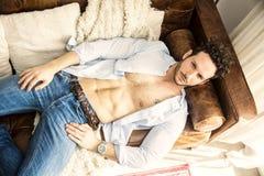单独说谎在长沙发的赤裸上身的性感的男性模型 免版税库存图片