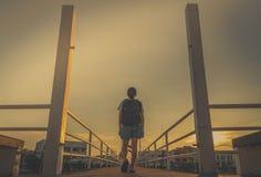 单独走与在桥梁的背包的亚裔妇女游人在城市在日落的晚上与黄色天空 走开 免版税库存图片