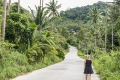 单独走在山路的女孩在泰国酸值的Phangan密林 免版税库存图片