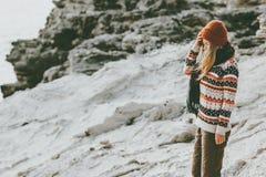 单独走在岩石海边旅行生活方式时尚概念冬天的妇女旅客假期室外 免版税图库摄影