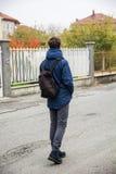 单独走在有背包的街道的十几岁的男孩 免版税库存照片