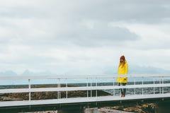 单独走在桥梁旅行生活方式情感概念的妇女假期室外黄色雨衣衣物有雾的山 库存图片