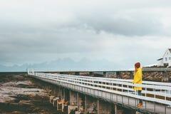 单独走在桥梁旅行生活方式情感概念的妇女游人假期室外黄色雨衣衣物有雾的山 免版税图库摄影