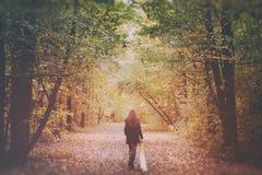 单独走在森林的哀伤的妇女 免版税库存图片