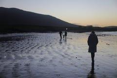 单独走在海滩的妇女在日落前 免版税库存照片