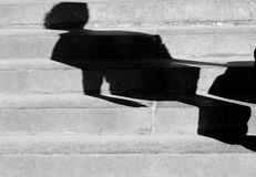 单独走城市台阶的妇女的残破的阴影 库存图片