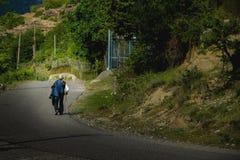 单独走沿路的老人 免版税库存照片