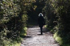 单独走资深白肤金发的妇女 免版税库存图片