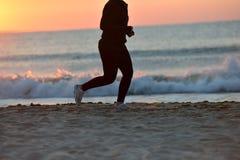 单独跑沿海滩的一个女孩的剪影  免版税库存图片