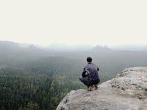 单独远足者背面图黑暗的室外衣服的坐边缘 在山谷上的锋利的岩石峰顶 免版税库存图片