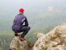 单独远足者背面图黑暗的室外衣服的坐边缘 在山谷上的锋利的岩石峰顶 库存照片