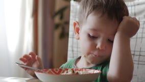 单独逗人喜爱的矮小的婴孩吃与一把匙子的粥从板材,健康吃的概念 股票视频