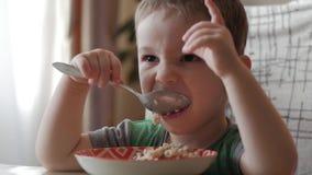 单独逗人喜爱的矮小的婴孩吃与一把匙子的粥从板材,健康吃的概念 股票录像