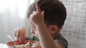单独逗人喜爱的矮小的婴孩吃与一把匙子的粥从板材,健康吃的概念 影视素材