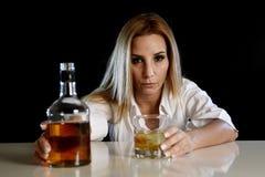 单独醉酒的醺酒的妇女与苏格兰威士忌酒瓶和玻璃的被浪费的沮丧的面孔的 免版税库存照片