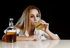单独醉酒的醺酒的妇女喝从苏格兰威士忌酒玻璃的被浪费的沮丧的面孔的 免版税图库摄影