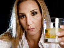 单独醉酒的醺酒的妇女拿着苏格兰威士忌酒玻璃的被浪费的沮丧的面孔的被浪费和被压下 免版税图库摄影