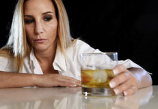 单独醉酒的醺酒的妇女看起来被浪费的沮丧的面孔的举行和周道对苏格兰威士忌酒玻璃 图库摄影