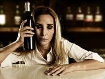单独醉酒的醺酒的白肤金发的妇女浪费的沮丧与在酒吧的红葡萄酒瓶 图库摄影
