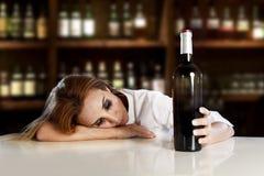 单独醉酒的醺酒的白肤金发的妇女浪费的沮丧与在酒吧的红葡萄酒瓶 免版税图库摄影