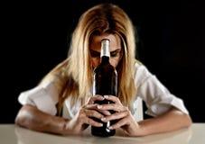 单独醉酒的醺酒的白肤金发的妇女浪费的沮丧以红葡萄酒瓶遭受的宿酒 免版税图库摄影