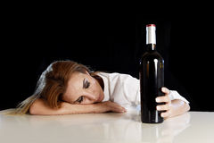 单独醉酒的醺酒的白肤金发的妇女浪费的沮丧以红葡萄酒瓶遭受的宿酒 免版税库存图片
