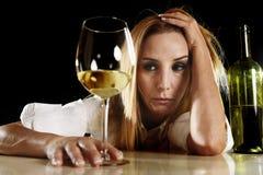单独醉酒的醺酒的白肤金发的妇女被浪费的沮丧的饮用的白葡萄酒玻璃遭受的宿酒的 免版税库存照片