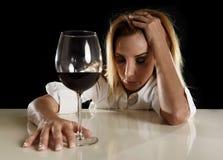 单独醉酒的醺酒的白肤金发的妇女被浪费的沮丧的饮用的红葡萄酒玻璃遭受的宿酒的 免版税库存照片