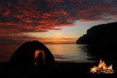 单独野营与在海滩的营火,红色天空日落bac的女孩 免版税图库摄影