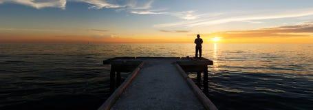 单独钓鱼在日落期间的孤独的人 免版税图库摄影