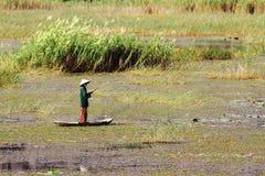 单独钓鱼在竹小船的人 免版税图库摄影
