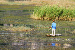 单独钓鱼在竹小船的年轻人 库存照片