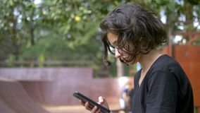 单独青少年的男孩使用以冰鞋公园为背景的一个手机 当其他孩子有效地放松时 影视素材