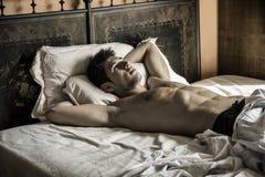 单独说谎在他的床上的赤裸上身的性感的男性模型 免版税库存照片