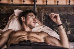单独说谎在他的床上的赤裸上身的性感的男性模型 图库摄影