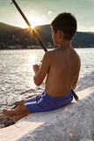 单独fisging在日落的男孩 库存照片