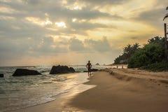 单独Wlking在日落期间的海滩在斯里兰卡的海岛上、地方渔夫和美丽的干净的海滩和波浪 库存图片