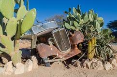 单粒宝石,纳米比亚- 2014年7月05日:仙人掌树篱的生锈的经典汽车修造的零件在单粒宝石的 库存照片