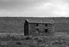 单色图象的一间老被放弃的石农舍在高荒野的绿色牧场地与多云阴暗天空 免版税库存图片